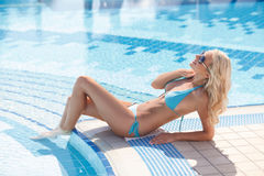 Women on poolside. Side view of attractive young women in bikini. Women on poolside. Side view of attractive young woman in bikini lying on the poolside Stock Photos