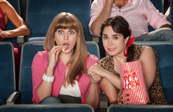 Women With Popcorn Holding Hands Stock Photography