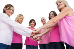 Women posing in circle holding hands looking at camera wearing p. Women posing in circle holding hands wearing pink for breast cancer looking at camera on white Royalty Free Stock Photos