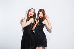 Women posing in night dress with glass of champagne Royalty Free Stock Photos
