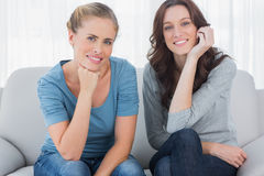 Women posing while sitting on the couch Royalty Free Stock Photos