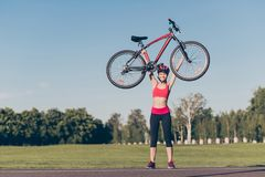 Women power! Fit female athlete lifted her modern bike above the. Head in helmet. She was riding outdoors in nice spring park Royalty Free Stock Image