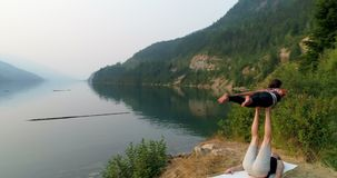 Women practicing acroyoga near lakeside 4k. Women practicing acroyoga near lakeside at dawn 4k stock footage