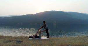 Women practicing acroyoga near lakeside 4k. Women practicing acroyoga near lakeside at sunset 4k stock video footage