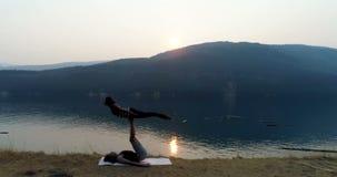 Women practicing acroyoga near lakeside 4k. Women practicing acroyoga near lakeside at sunset 4k stock footage
