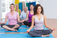 Women practicing lotus position in gym Stock Photos