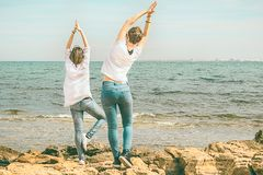 Women practicing yoga on the beach. Hands up. Dressed in white Stock Photo