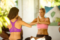 Women practicing yoga while sitting on exercise mat Stock Images