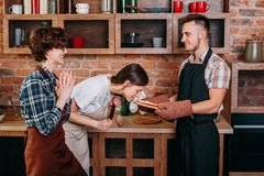 Women praise friend for cooking delicious pizza. Women praise their friend for cooking delicious meals. Young happy men with pizza and cheerful girls applauding Stock Image