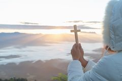 Women pray to god with the cross on the mountain background with morning sunrise. Woman Pray for god blessing to wishing have a. Better life. Christian life stock images