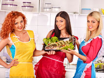 Women prepare fish in oven Stock Image