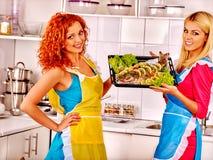 Women prepare fish in oven Stock Image