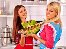 Women prepare fish in oven. Royalty Free Stock Photos