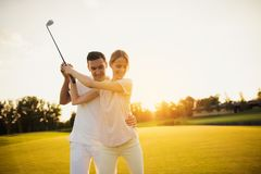 A man is teaching his girlfriend how to play golf at sunset Royalty Free Stock Images