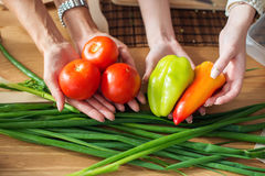 Women preparing dinner in a kitchen holding vegetables hands dieting healthy food cooking at home. Royalty Free Stock Photos