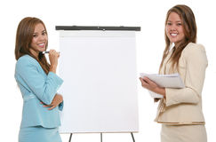 Women Presenting. Two pretty women making a business presentation on flipchart Royalty Free Stock Photography