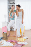 Women pretending to sing with shopping bags and clothes on floor Stock Photography
