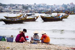Women processing seashells with fishing boats in background on February 7, 2012 in Mui Ne, Vietnam. Stock Image