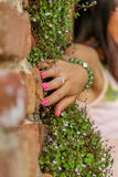 Women propping up the brick-flowers wall Royalty Free Stock Image