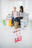 Women with purchases and shopping bag on foreground Stock Images