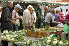 Women purchasing fresh cauliflower from the market in Husum. Market place in the Seaport City Husum in the North of Germany with people Royalty Free Stock Image
