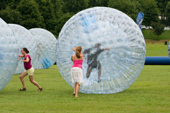 Women Push Large Zorbs Around Grass Field At Summer Festival stock photos
