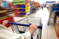 Women pushing trolley cart in supermarket. With motion blur Royalty Free Stock Photos