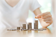 Women put coin stack money. For money growth concept Stock Photos