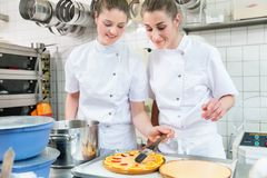 Women putting fruit on cakes in pastry bakery Royalty Free Stock Photos