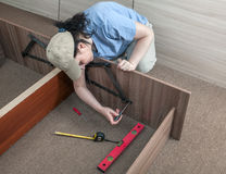 Women putting together self assembly furniture. Royalty Free Stock Image