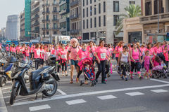 Women race against breast cancer. Barcelona, Spain - November 8, 2015: Women and a man in pink T-shirts march in the center of Barcelona on day dedicated to Royalty Free Stock Photos