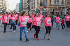 Women race against breast cancer. Barcelona, Spain - November 8, 2015: Women in pink T-shirts march in the heart of the city on day dedicated to women race Royalty Free Stock Images