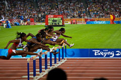Women racing 100M hurdles Royalty Free Stock Photography