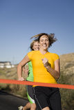 Women racing to finish line. Two women with smilies racing to the finish line during a race Royalty Free Stock Photography