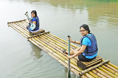 Women Rafting. Two individuals, mother and teenage daughter, rafting in a river on a bamboo raft Royalty Free Stock Image