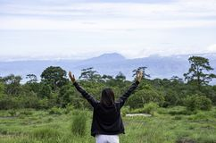 Women raise their arms looked at the mountains and trees at Phu Hin Rong Kla National Park , Phetchabun in Thailand.  royalty free stock photography