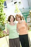 Women with rakes in garden. Mother and daughter holding rakes gardening outside Royalty Free Stock Photo