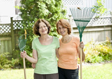 Women with rakes in garden. Mother and daughter holding rakes gardening doing yard work outside Royalty Free Stock Images