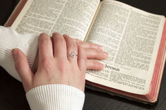 Women Reading the Bible. With her hands resting on the bible stock photography