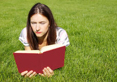 Women reading book. Young women with red book on the green grass Stock Images