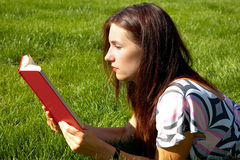 Women reading book. Young women with red book on the green grass Royalty Free Stock Photo