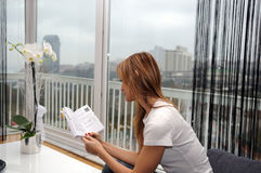 Women reading a book. Close-up of a young woman sitting on a sofa; and reading a book Stock Photos