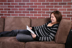 Women reading book. Young woman reading book on couch royalty free stock image