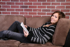 Women reading book. Young woman reading book on couch stock photos