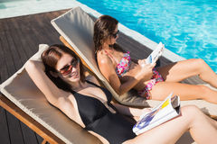 Women reading books on sun loungers by swimming pool. Side view of two young women reading books on sun loungers by swimming pool stock image