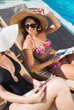 Women reading books on sun loungers by swimming pool Royalty Free Stock Photography