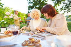 Women reading cookbook while eating cake. Two elderly women reading cookbook while eating cake in a garden Stock Photo
