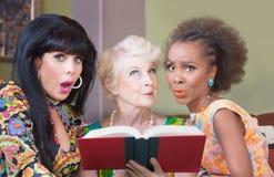 Women Reading a Romance Novel. Diverse beautiful mature women reading a romance novel Royalty Free Stock Image