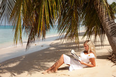 Women reading under palm tree Royalty Free Stock Images