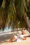Women reading under palm tree Stock Photo